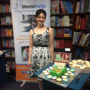 Susie at her launch party, in front of the info banner for HemiHelp, the charity for people and families affected by hemiplegia